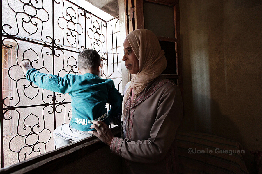 Saida, 32 years old, single mother stands by the window with her son in her place. She lives in a single space of around 12  square meters without any running water facilities, neither amenities or fridge.  Daoudiat District - Marrakech 26 April 2013