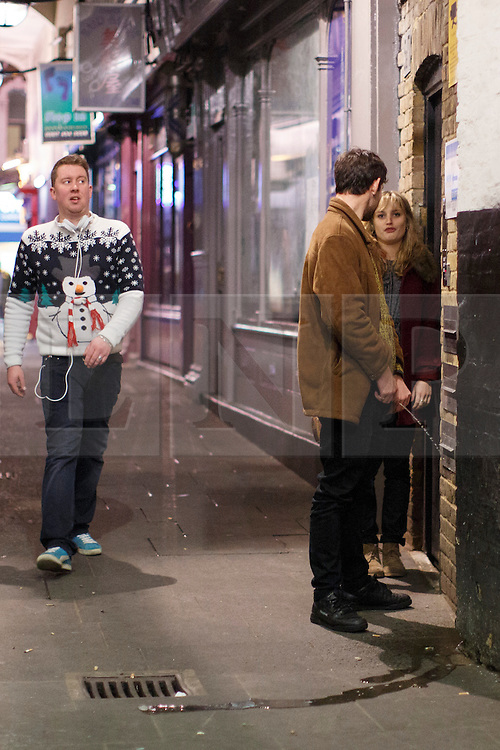 """© licensed to London News Pictures. London, UK 14/12/2013. A """"Mad Friday"""" reveller urinating in the street in Soho, London whilst enjoying the last Friday night out before Christmas, which is also the busiest night of the year for emergency services. Photo credit: Tolga Akmen/LNP"""
