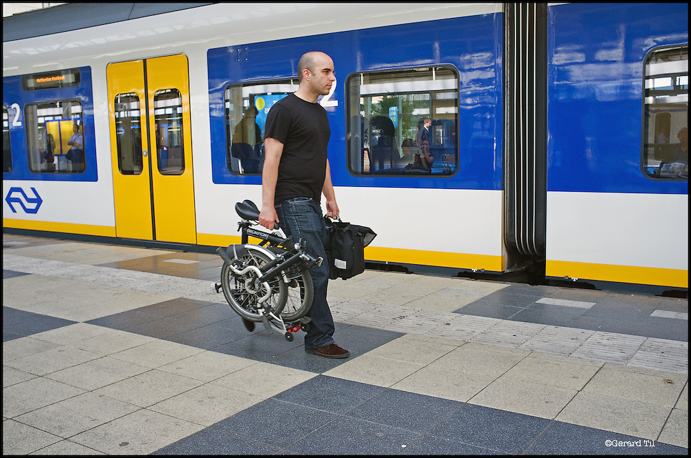 Amsterdam, 17-08-2011 Amstelstation, man met  Brompton vouwfiets loopt langs stilstaande trein. Foto: Gerard Til/Hollandse Hoogte