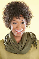 Portrait of an African American woman with a stole round her neck smiling over colored background