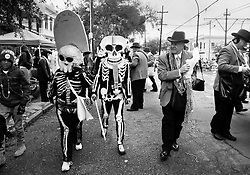 17 Feb 2015. New Orleans, Louisiana.<br /> Mardi Gras Day. Walking with Skeletons. <br /> The Skeleton Krewe mingles with Pete Fountain's Half Fast Walking Club on St Charles Avenue. The Skeleton Krewe meets before dawn beside a cemetery in Uptown New Orleans. They then walk several miles Along Saint Charles Avenue to the French Quarter to celebrate Mardi Gras Day.<br /> Photo; Charlie Varley/varleypix.com