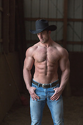 muscular shirtless cowboy with great abs, big arms and nice chest inside a barn