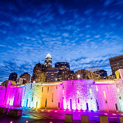 Charlotte skyline at night photo with Romare Bearden Park waterfall fountain and downtown Charlotte buildings against a blue sky and clouds. Charlotte, North Carolina is a major city in the Eastern United States of America.