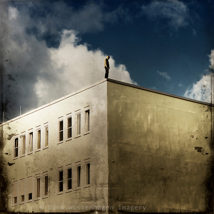 Composing - a man standing at the roof's edge of a building looking down.