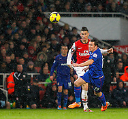 Picture by Mike  Griffiths/Focus Images Ltd +44 7766 223933<br /> 01/01/2014<br /> Lukas Podolski of Arsenal and Don Cowie of Cardiff City during the Barclays Premier League match at the Emirates Stadium, London.