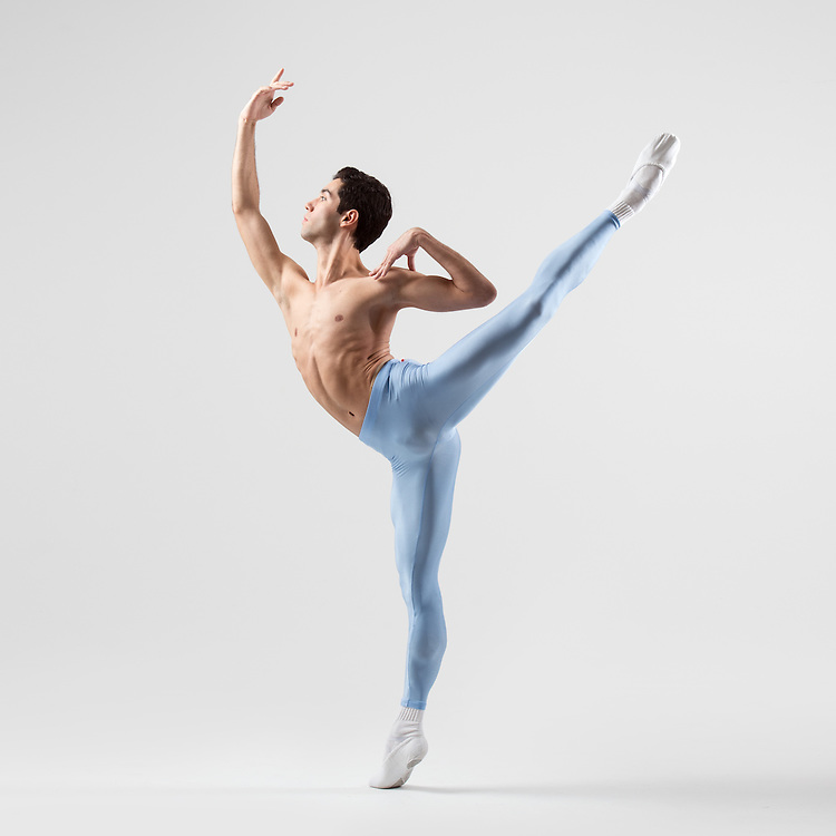 Classical male ballet dancer, Nicolas Moreno, in an arabesque in blue tights, in the photo studio on a light gray background. Photograph taken in New York City by photographer Rachel Neville.