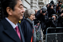 © Licensed to London News Pictures. 10/01/2019. London, UK. Prime Minister Theresa May (C) and Prime Minister of Japan Shinzo Abe (L) walk past the media as they arrive in Downing Street for a bilateral meeting. Photo credit: Rob Pinney/LNP