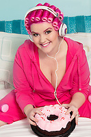 Portrait of a happy young woman wearing headphones sitting on bed with cake