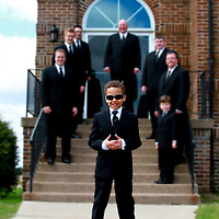 Grooms men in black pose in front of the church