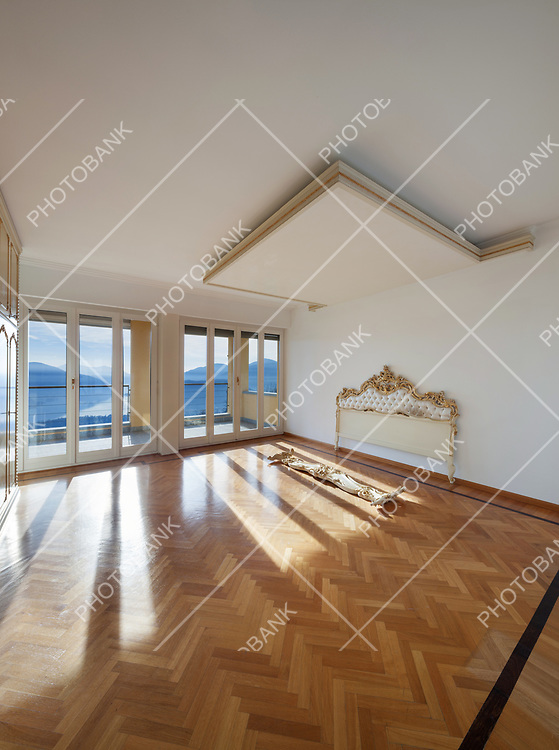 interior of an house, empty room with headboard, parquet floor and white walls