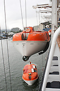 Abandon Ship Drill. Lifeboat. This vessel, for use in an emergency if the crew and passengers have to abandon ship, is lowered to the surface of the sea using the winches and pulleys seen here.