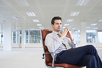 Office worker sitting in swivel chair in empty office space
