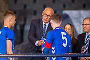 Former Rangers player Mark Hateley presents the SFA Youth Cup to the winning captain Daniel Finlayson (#5) of Rangers FC at the end of the Scottish FA Youth Cup Final match between Celtic and Rangers at Hampden Park, Glasgow, United Kingdom on 25 April 2019.