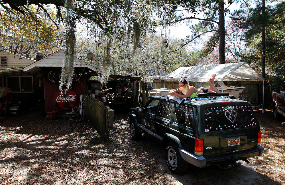 "Allison Kopanski, 18, of Beaufort, reads from a book while basking in the sun on top of her Jeep at her home in the Pigeon Point neighborhood in Beaufort on March 17, 2015.  ""Sun was out but it was too far to get to the beach,"" said Kopanski."