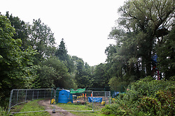 Denham, UK. 13 July, 2020. HS2 security guards monitor a compound established to facilitate tree felling in Denham Country Park. Environmental activists from HS2 Rebellion are currently occupying tree houses adjacent to the site in order to try to hinder or prevent progress on the £106bn HS2 high-speed rail project.