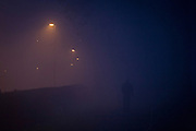 The silhouette of a figure walking through a park, with a foggy residential street in the background.