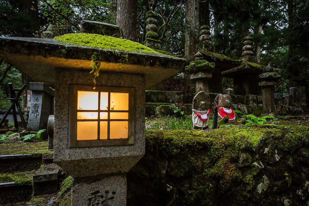 A lit up lantern stands illuminating two small statues of Jizo: buddhist deities that look after dead children's souls and help them pass on from the land of the living to the land of the dead.