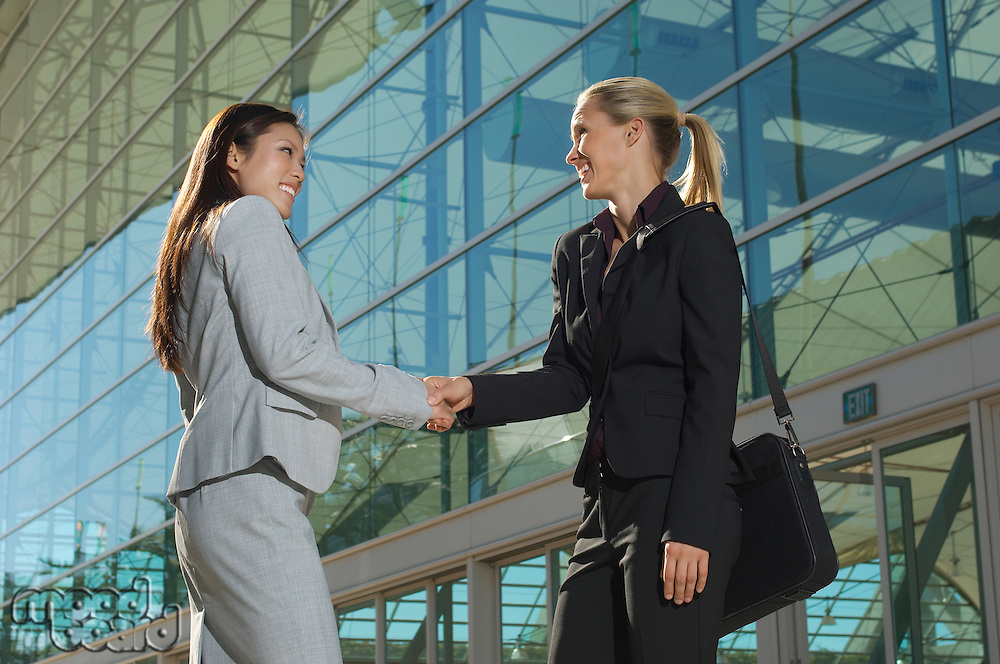 Two businesswomen shaking hands outside office building