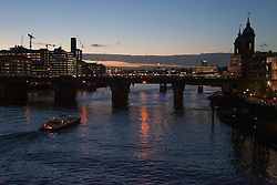 London. <br /> A boat crosses Thames river with at  London Bridge area at twilight, London, United Kingdom. Monday, 4th November 2013. Picture by Daniel Leal-Olivas / i-Images