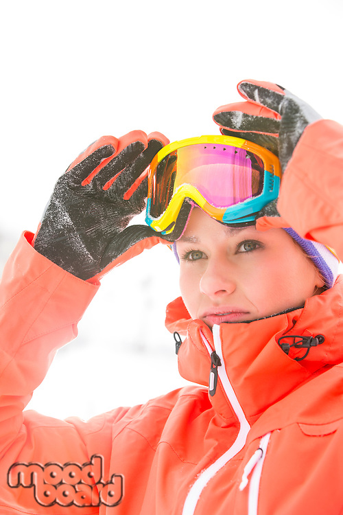 Confident young woman wearing ski goggles outdoors