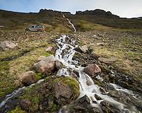 A small stream running down Kjörvogshlíð, Land Rover parked on road. Strandir area, Northwest Iceland.
