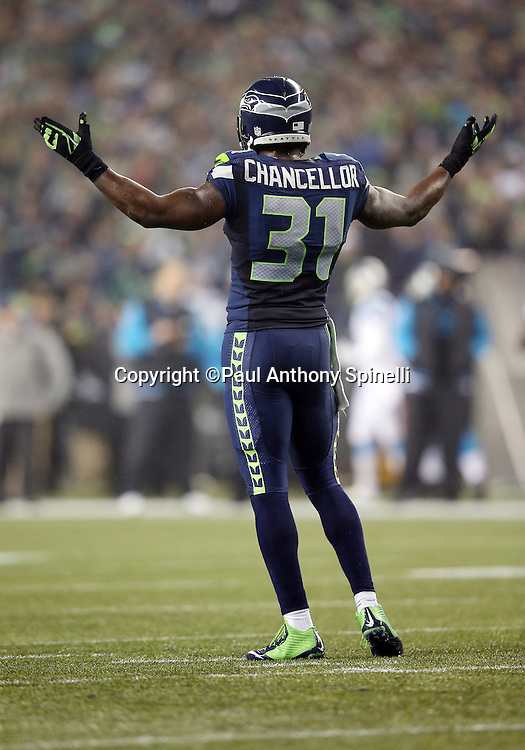 Seattle Seahawks strong safety Kam Chancellor (31) waves his arms as he tries to fire up the fans on a second quarter fourth down stand by the Seahawks defense during the NFL week 19 NFC Divisional Playoff football game against the Carolina Panthers on Saturday, Jan. 10, 2015 in Seattle. The Seahawks won the game 31-17. ©Paul Anthony Spinelli