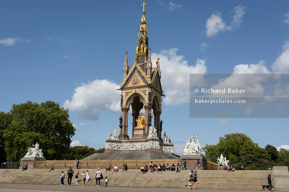 The Albert Memorial in Kensington Park, on 20th August 2019, in London, England. The Albert Memorial, directly north of the Royal Albert Hall in Kensington Gardens, London, was commissioned by Queen Victoria in memory of her beloved husband Prince Albert, who died in 1861. Designed by Sir George Gilbert Scott in the Gothic Revival style, it takes the form of an ornate canopy or pavilion 176 feet tall, in the style of a Gothic ciborium over the high altar of a church, sheltering a statue of the prince facing south. It took over ten years to complete, the £120,000 cost met by public subscription.
