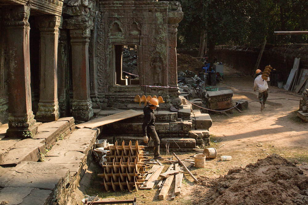 Asia, Cambodia, Siem Reap, Workers carry drill parts during restoration work at crumbling remains of Ta Prohm pagoda at Angkor Wat