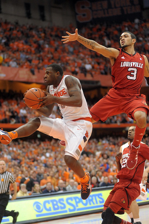 Syracuse Orange guard Dion Waiters (3) glides to the hoop past Louisville Cardinals guard Peyton Siva (3) in the second half at the Carrier Dome in Syracuse, NY. Syracuse defeated Louisville in front of a crowd of 33,205 as the Orange finish the season as regular season Big East champions at 30-1.