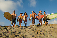 Six surfers carrying surfboards running on beach