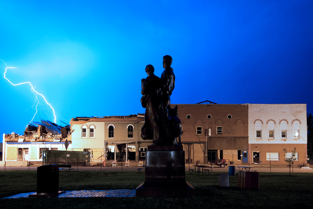 "Lightning flashes through the sky over downtown Elmwood, IL as Lorado Taft's ""The Pioneers"" statue looks on. The buildings in the background were damaged in a tornado several weeks before."