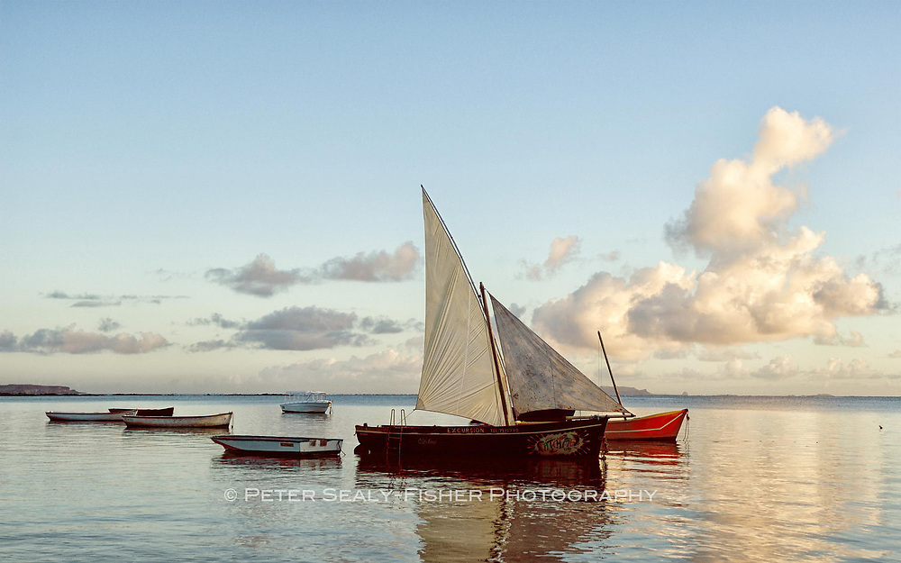 A sleepy fishing village in Mauritius, with boats floating idly in calm water under pastel skies and clouds