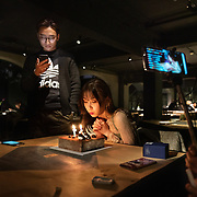 Nai Nai, a 23-year-old live-streamer in Shanghai, blows out the candles on her birthday cake as her male fans who were attending her party watch her on their smartphones. 