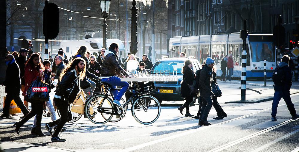 AMSTERDAM - Drukte in het verkeer in het centrum van Amsterdam met voetgangers trams toeristen fietsen , auto's  Het verhaal gaat dus over de toenemende drukte in de binnenstad nav nieuwjaarstoespraak Van der Laan. COPYRIGHT ROBIN UTRECHT