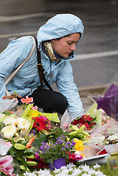 Parliament Square, Westminster, London, June 17th 2016. Following the murder of Jo Cox MP friends and members of the public lay flowers, light candles and leave notes of condolence and love in Parliament Square, opposite the House of Commons. PICTURED: A woman lays flowers as the rain falls on Parliament Square.