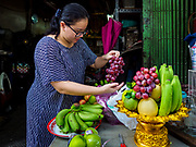 """05 SEPTEMBER 2017 - BANGKOK, THAILAND: A woman sets a table for a banquet on Hungry Ghost Day. The Ghost Festival is a Buddhist and Taoist holy day celebrated on the 15th day of the 7th lunar month. It is primarily celebrated in China and Chinese communities outisde China. In Thailand, it's celebrated in Thai-Chinese communities in Bangkok, Phuket and Chiang Mai.  On that day ghosts and spirits, including those of the deceased ancestors, come out from the lower realm to visit the living. Families prepare elaborate banquets for the spirits and burn """"ghost money"""" for the spirits to use in the other realm. It is a day for venerating dead relatives.      PHOTO BY JACK KURTZ"""