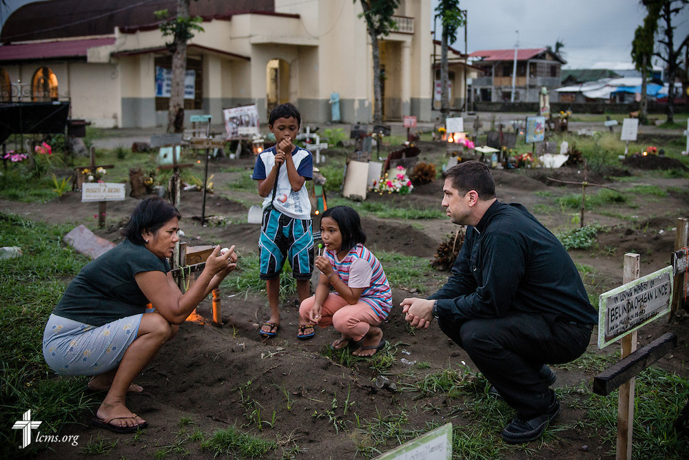 The Rev. Ross Johnson, director of LCMS Disaster Response, comforts a family who lost relatives in Typhoon Haiyan at a graveyard in Tacloban, Leyte Province, Philippines, on Friday, March 14, 2014. LCMS Communications/Erik M. Lunsford