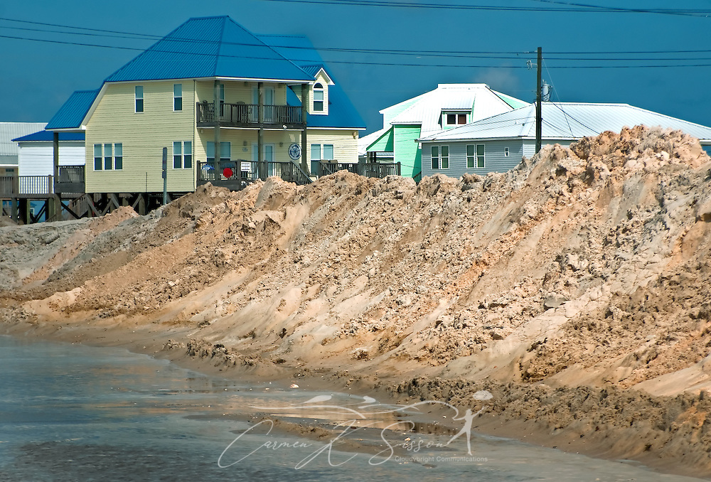 Beach homes are almost completely obscured by sand piles on the west end of Dauphin Island, Alabama, where efforts to protect the island from oil threatening as a result of the Deepwater Horizon rig explosion earlier in the month were heavily underway May 7, 2010. City officials hope the sand will protect the homes if the oil reaches the island. (Photo by Carmen K. Sisson/Cloudybright)