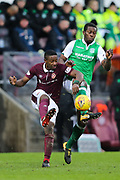 Arnaud Djoum (#10) of Heart of Midlothian clears the ball upfield under pressure from Marvin Bartley (#6) of Hibernian during the William Hill Scottish Cup 4th round match between Heart of Midlothian and Hibernian at Tynecastle Stadium, Gorgie, Scotland on 21 January 2018. Photo by Craig Doyle.