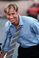 Blond man with blue eyes smiling in a shirt and loose tie
