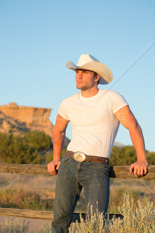 hot cowboy leaning on a fence watching the sunset