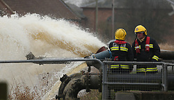 © London News Pictures. 31/01/2014. Burrowbridge, UK. Firemen use pumps to move flood water from the village of Burrowbridge in Somerset on the Somerset levels.  The area has been hit severely by recent flooding which is forecast to get worse over the weekend . Photo credit: Jason Bryant/LNP