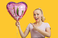 Portrait of surprised young woman holding heart shaped birthday balloon over yellow background