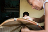 "Vietnamese artisans meticulously stitch conical hats, Chuong Village, Ha Tay Province, Vietnam, Southeast Asia, 2013. This handicraft village specializes in the fabrication of the conical hat, known as ""non"" in Vietnamese."