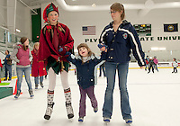"""""""Elf"""" Tristan Amburg skates alongside Bette Fallon and her sister Kristi Zwald during Plymouth Ice Arena's Skate with Santa event Sunday afternoon.  (Karen Bobotas/for the Laconia Daily Sun)"""