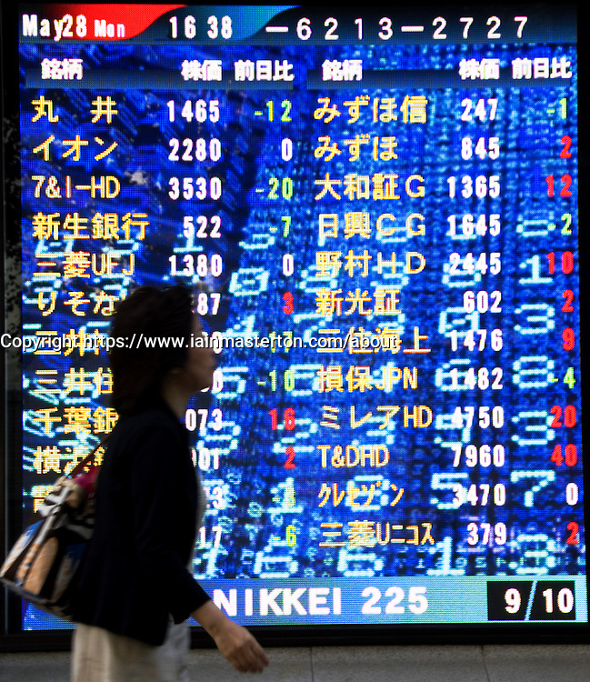 Woman walks past large stock price display screen in central Tokyo Japan