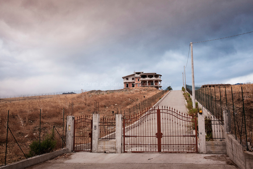 San Luca, Italy - 2 September, 2012: An unfinished home is seen here in San Luca, a mafia stronghold in Calabria, Italy, on September 2nd, 2012. San Luca, in the words of a study published in 2005 by Italy's domestic intelligence service, is the cradle of the 'Ndrangheta and its epicentre. The unfinished concrete buildings, which are very common throughout Calabria, are the result of the inability to go beyond the merely useful, creating functionality without regard for form.<br /> <br /> Calabria is one of the poorest Italian regions which suffers from lack of basic services (hospitals without proper equipment, irregular electricity and water), the product of disparate political interests vying for power. The region is dominated by the 'Ndrangheta (pronounced en-Drang-get-A), which authorities say is the most powerful in Italy because it is the welthiest and best organized.<br /> <br /> The region today has nearly 20 percent unemployment, 40 percent youth unemployment and among the lowest female unemployment and broadband Internet levels in Italy. Business suffer since poor infrastructure drives up transport costs.<br /> <br /> Last summer the European Union's anti-fraud office demanded that Italy redirect 380 million euros in structural funding away from the A3 Salerno - Reggio Calabria highway after finding widespread evidence of corruption in the bidding processes.