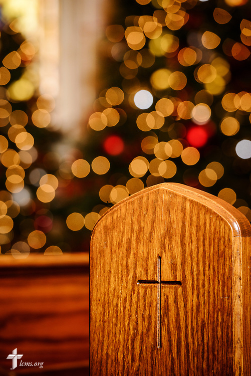An etched cross on a pew is framed by Christmas tree lights at Holy Cross Lutheran Church, Collinsville, Ill., on Monday, Nov. 27, 2017. LCMS Communications/Erik M. Lunsford