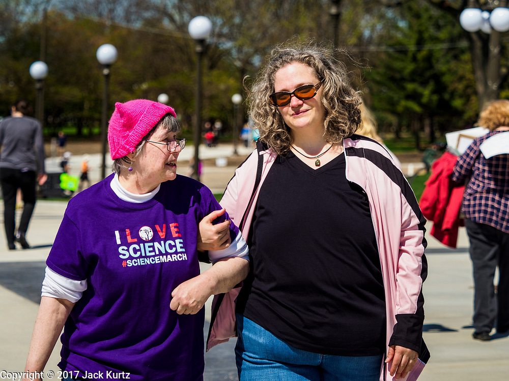 "22 APRIL 2017 - ST. PAUL, MN: A woman wearing the ""pink pussy hat"" from the women's march in January arrives at the March for Science at the Minnesota State Capitol. More than 10,000 people marched from the St. Paul Cathedral to the Minnesota State Capitol in St. Paul during the March for Science. March organizers said the march was non-partisan and was to show support for the sciences, including the sciences behind climate change and vaccines.      PHOTO BY JACK KURTZ"