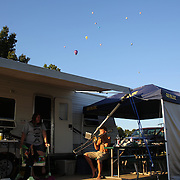 A young boy practices his trombone at Hideaway Hills Family Campground in rural Michigan near Battle Creek as hot air balloons pass overhead during competition in the 20th FAI World Hot Air Ballooning Championships. Battle Creek, Michigan, USA. 22nd August 2012. Photo Tim Clayton